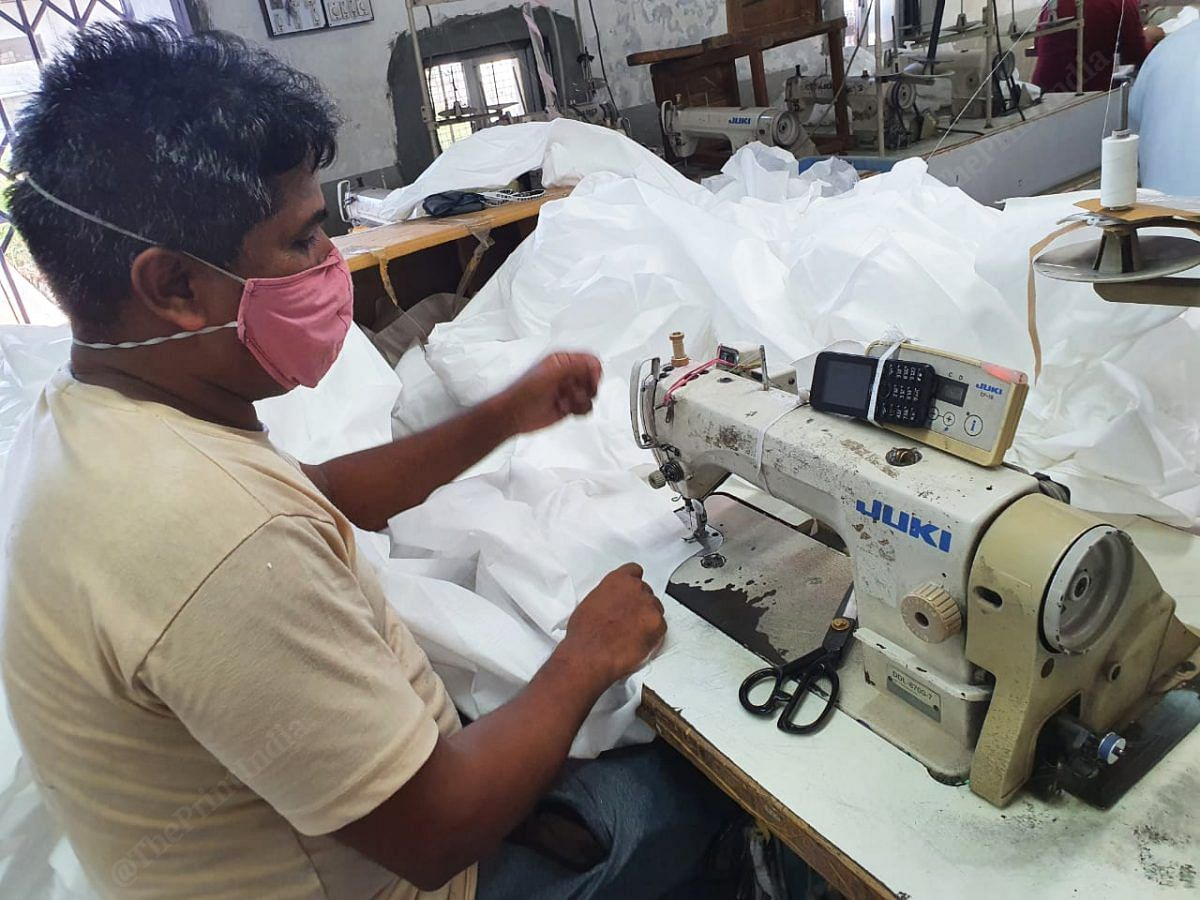 Once the stitching is done, the overall is sent to another team for inspection. Here the team looks for any loose threads or knots that they can trim out. Any spots on the cloth are also sanitised and cleaned | Photo: Soniya Agarwal | ThePrint