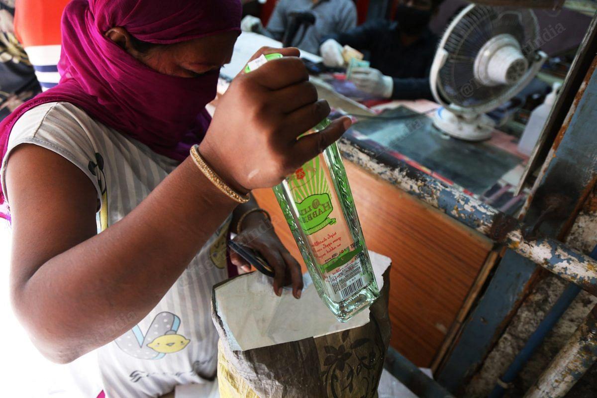 A woman put a bottle of alcohol inside the bag | Photo: Manisha Mondal | ThePrint