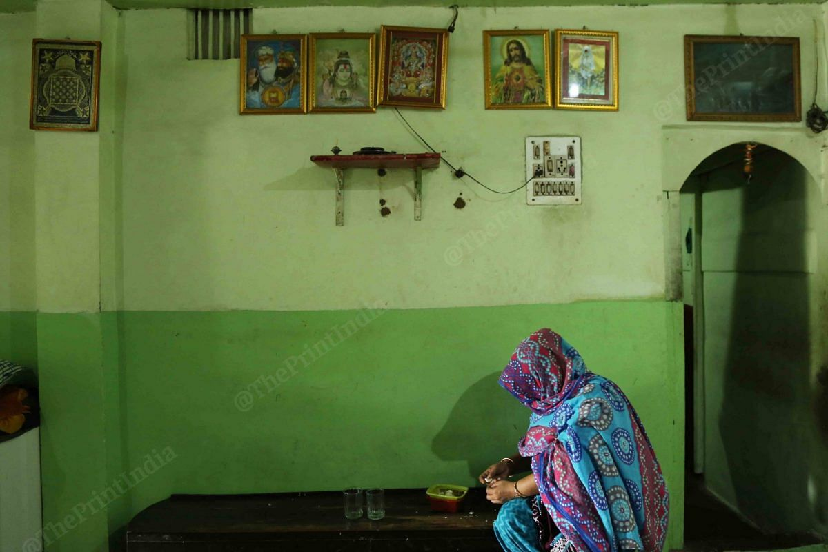 A women does some chores in a room where there are photographs of gods from different religion   Photo: Manisha Mondal   ThePrint