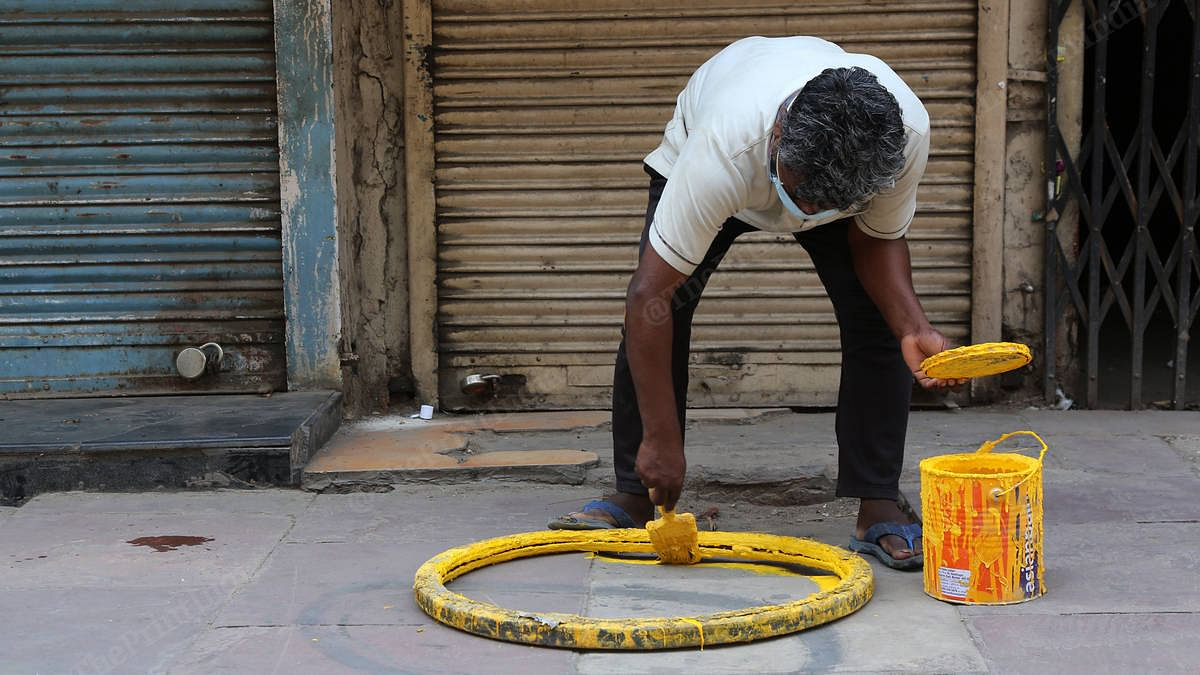 A worker paints a social distancing circle outside a liquor store in Daryaganj | Photo: Manisha Mondal | ThePrint