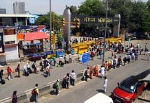 Passengers wait outside New Delhi railway station to board trains to their home states, on 12 May 2020
