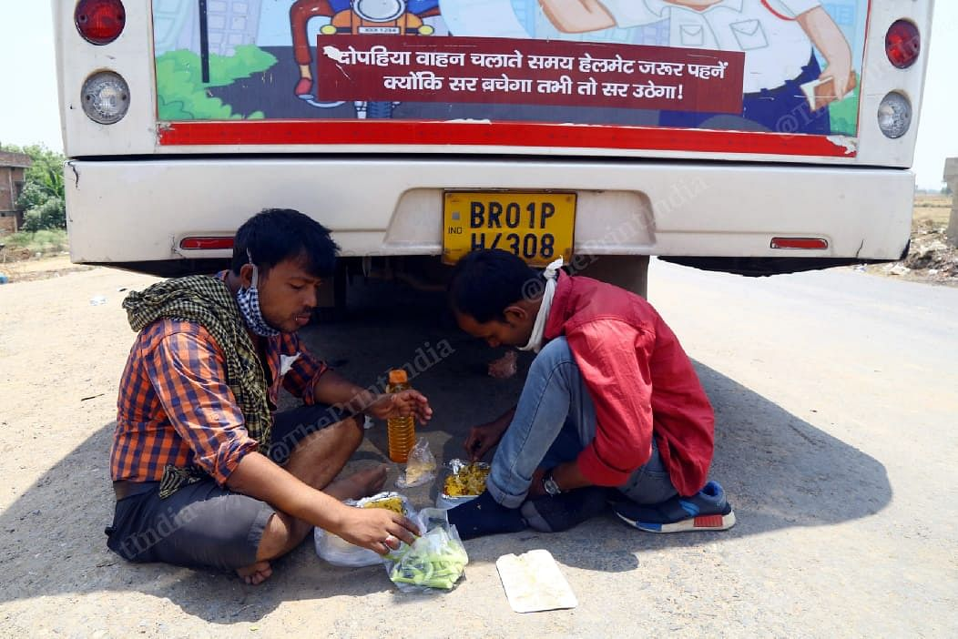 A group of migrants has a meal while waiting to catch the bus | Suraj Singh Bisht | ThePrint