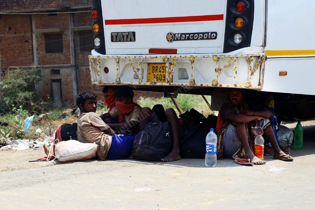 Migrants take a moment of rest under a bus | Suraj Singh Bisht | ThePrint