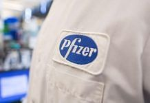 The Pfizer logo on the lab coat of an employee at the company's research and development facility in Cambridge, Massachusetts. | Bloomberg