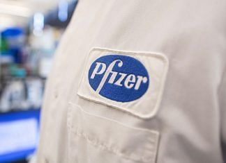 The Pfizer logo on the lab coat of an employee at the company's research and development facility in Cambridge, Massachusetts.   Bloomberg
