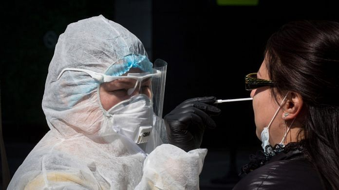 A medical worker dressed in personal protective equipment (PPE) takes a nasopharyngeal swab sample from a visitor at a Chaika Clinic mobile covid-19 sample-collection site in Moscow International Business Center (MIBC) | Photographer: Andrey Rudakov | Bloomberg