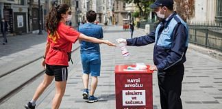 A municipal worker squirts hand sanitizer into the hand of a pedestrian in Istanbul on May 14. | Bloomberg