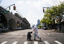 A man wearing a protective suit crosses a street in Queens, New York City on May 15 | Representational image | Bloomberg