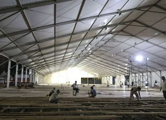 Workers lay flooring panels during the construction of a 1000 bed hospital for Covid-19 treatment at the Bandra Kurla Complex at night in Mumbai   Bloomberg