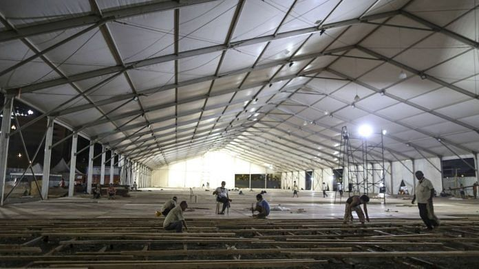 Workers lay flooring panels during the construction of a 1000 bed hospital for Covid-19 treatment at the Bandra Kurla Complex at night in Mumbai | Bloomberg