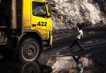 A worker is reflected in a puddle as he walks towards a truck at an open cast coal mine in Bastacolla Colliery in Jharia, Jharkhand | Photographer: Sanjit Das | Bloomberg photo