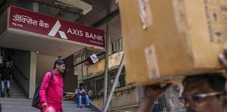 Pedestrians walk past an Axis Bank Ltd. branch in Mumbai, India. | Photographer: Dhiraj Singh | Bloomberg