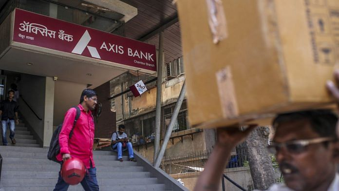 Pedestrians walk past an Axis Bank Ltd. branch in Mumbai, India. | Photographer: Dhiraj Singh | Bloomberg