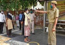 A Delhi homeguard conducts a thermal screening of passengers at a bus stop during the Covid-19 lockdown