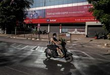 A motorcyclist wearing a protective mask rides past a Kotak Mahindra Bank Ltd. branch on a near-empty street in Mumbai, India. | Photographer: Dhiraj Singh | Bloomberg