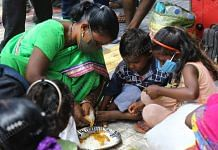 A worker serves food to her children outside the Secunderabad railway station | Suraj Singh Bisht/ThePrint