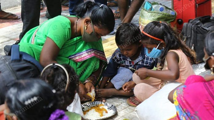 A worker serves food to her children outside the Secunderabad railway station   Suraj Singh Bisht/ThePrint