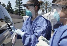 Nurses wearing PPE prepare to collect a nasal swab specimen from a patient at a Covid-19 drive-through testing site at the North Inland Live Well Escondido Center in Escondido, California, US (representative image) | Photo: Bing Guan | Bloomberg