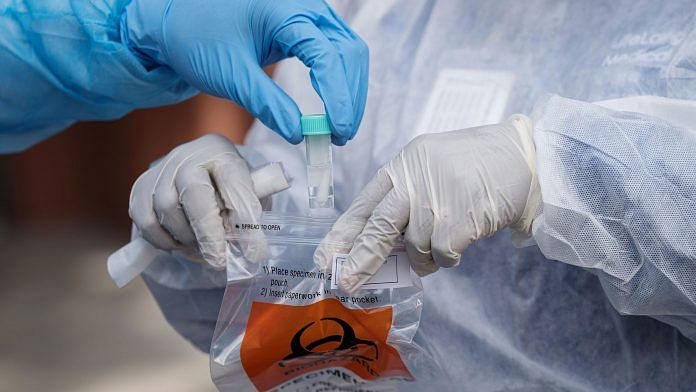 A medical worker drops a Covid-19 test sample into a plastic bag at a testing site in Berkeley, California, US | Photographer: David Paul Morris | Bloomberg