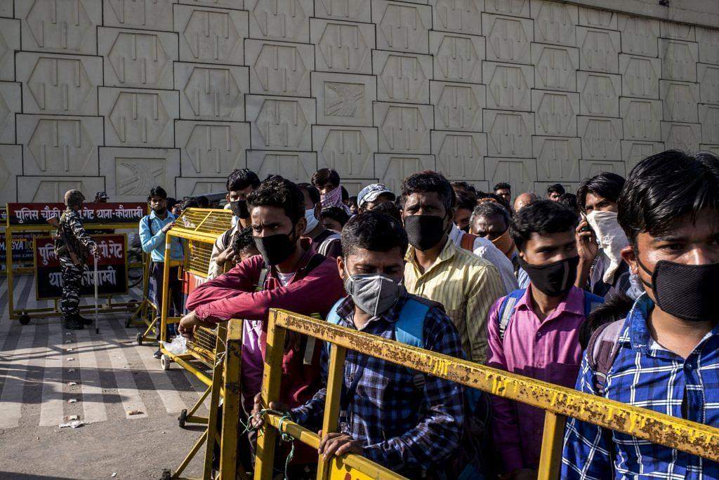 Migrant workers and their families are held behind a barrier at a police checkpoint in New Delhi, on March 28. | Photo: Anindito Mukherjee | Bloomberg