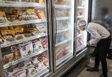 An employee arranges frozen chicken products in a freezer at a Big Bazaar hypermarket, operated by Future Retail Ltd. | Photographer: Dhiraj Singh | Bloomberg