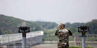 """A man wearing a T-shirt with the words """"Korea Army"""" looks across to the North Korean side of the border at the Imjingak pavilion near the Demilitarized Zone (DMZ) in Paju, South Korea 