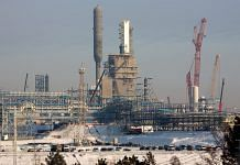 A methane extraction column towers above the site of the Gazprom PJSC Amur gas processing plant in Siberia | Bloomberg