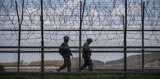 South Korean soldiers patrol along a barbed wire fence Demilitarized Zone (DMZ) separating North and South Korea, on the South Korean island of Ganghwa on April 23