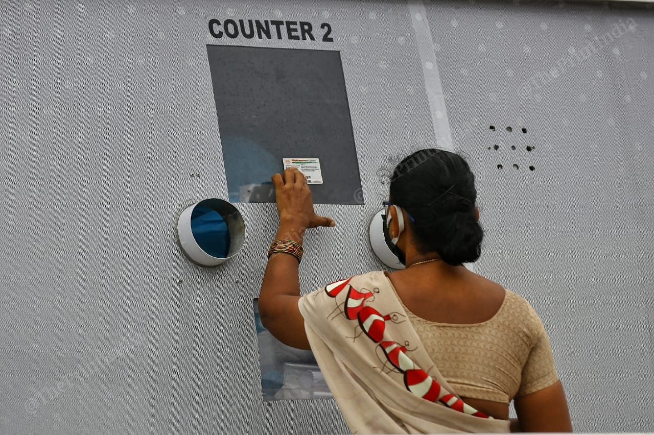 A woman shows her identity card for the details   Photo: Suraj Singh Bisht   ThePrint