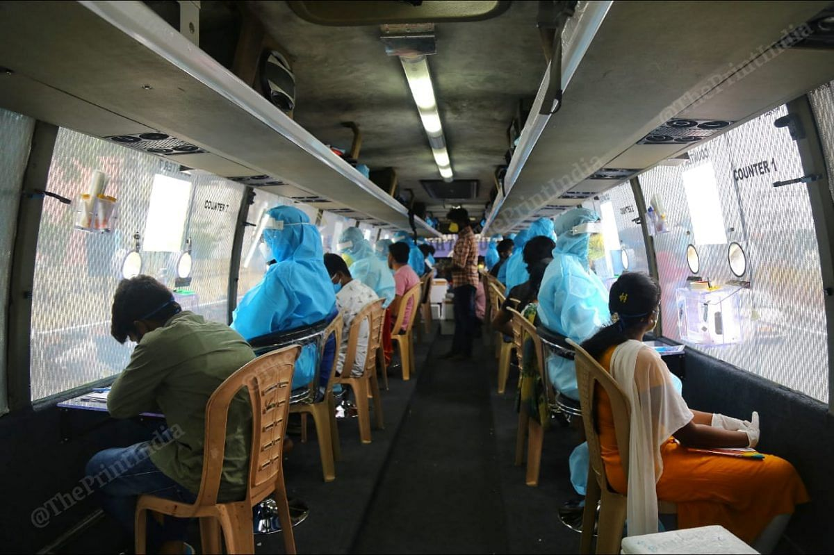 Lab technicians and doctors seated inside a mobile testing facility set up in a bus   Photo: Suraj Singh Bisht   ThePrint
