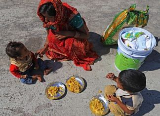 A migrant worker that was unable to catch a bus feeds her children on the side of National Highway 24 during Covid lockdown in Delhi