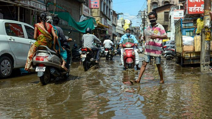 Vehicles pass through a waterlogged street after heavy monsoon rain, in Nagpur on 12 June 2020 | PTI