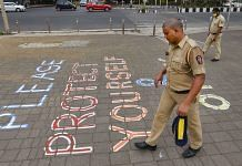 Representational image | Police personnel walk past a message that reads 'Please Protect Yourself And Others' at Marine Drive, during Covid pandemic | PTI