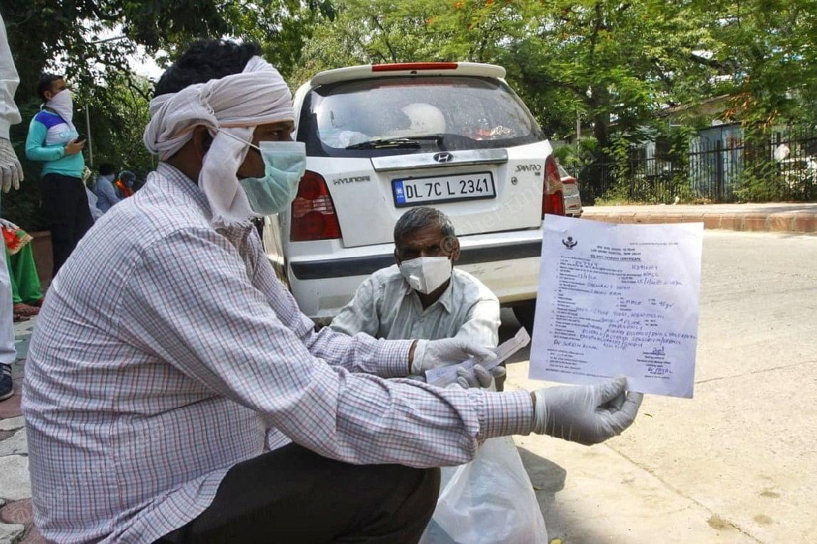 Rakesh Kumar holds up the death certificate for his father | Praveen Jain | ThePrint