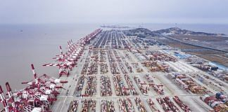 Shipping containers sit stacked next to gantry cranes at the Yangshan Deep Water Port | Bloomberg