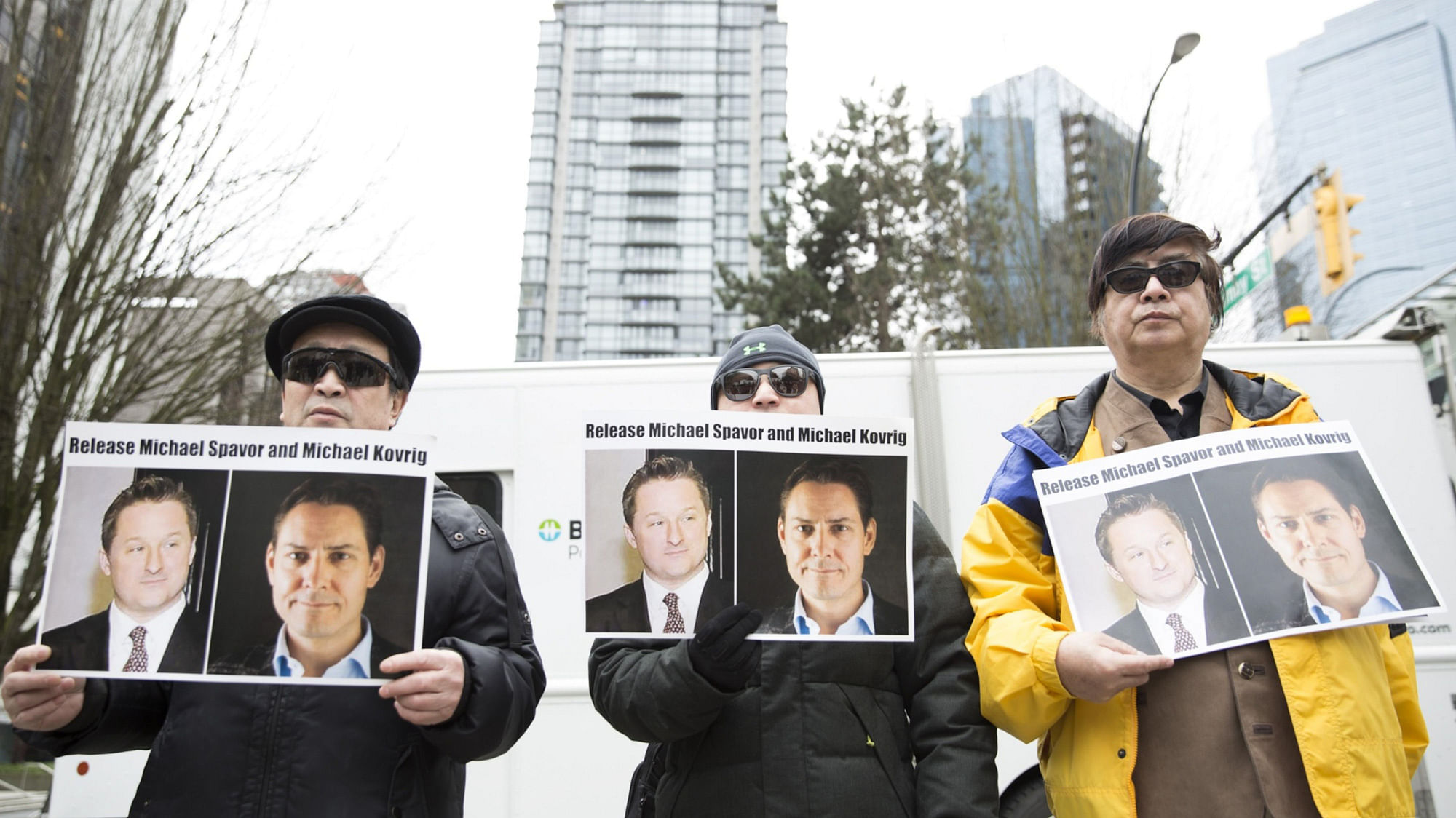 Protesters hold photos of Canadians Michael Spavor and Michael Kovrig, who are being detained by China, outside British Columbia Supreme Court, in Vancouver