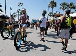 Cyclists ride along the Venice Beach boardwalk on May 25.