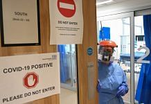 A medical worker in PPE suit holds the door, to a Covid-19 positive area, in the ICU at a hospital in Cambridge
