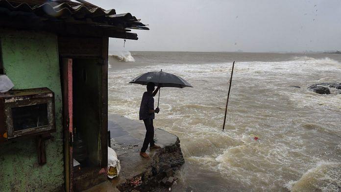A man stands near a shanty built on the edge of the Arabian Sea at Bandra, as the waves turn choppy ahead of Cyclone Nisarga expected landfall, in Mumbai   PTI