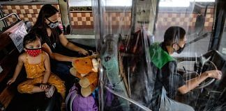 A driver sits behind a plastic covering for protection inside a bus on the first day of relaxed quarantine measures in Caloocan, Metro Manila, Philippines on 1 June