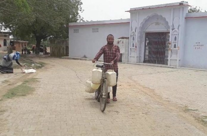 A man carrying water on his bicycle in a Jhansi village.   Photo: Prashant Srivastava/ThePrint