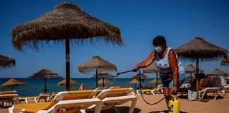 A worker wearing a protective face mask sprays disinfectant on sun loungers at Quarteira Beach in Quarteira, Algarve region, Portugal | Bloomberg