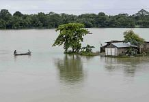 Villagers row a boat near a submerged house to cross a flooded area, in Morigaon district, Assam, 18 July | PTI