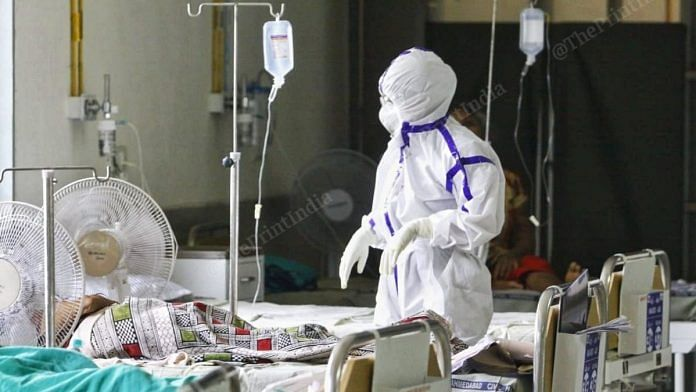 A health worker in PPE checks on a patient at a Covid centre in Ahmedabad | Praveen Jain | ThePrint
