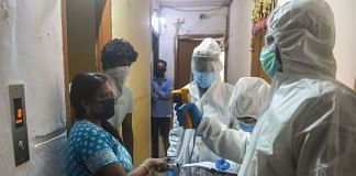 Health workers check the temperature of a woman during a Covid-19 screening drive at a residential building in Dharavi in Mumbai | PTI File Photo