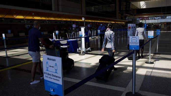 Passengers walk past thermal imaging cameras at Los Angeles International Airport (LAX) | Patrick T. Fallon | Bloomberg