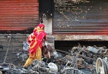 A woman walks through the burnt remains of vehicles set on fire during the Northeast Delhi riots earlier this year | File photo | Suraj Singh Bisht | ThePrint