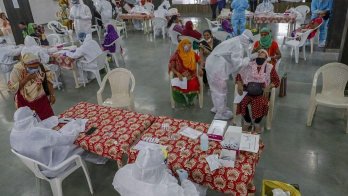 Healthcare workers wearing personal protective equipment (PPE) kits collect swab samples of municipal school teachers for Covid-19 test, in Ahmedabad. | PTI