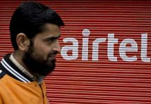 A man walks past a shutter of a closed store displaying the Bharti Airtel Ltd. logo. | Photographer: Brent Lewin | Bloomberg