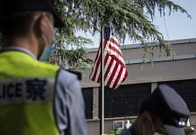Police officers stand near an American flag flown in front of the US Consulate General Chengdu in Chengdu on 26 July.